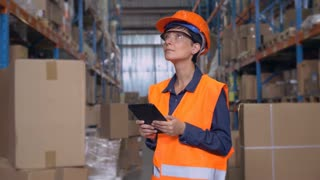 Manager woman working at warehouse. Attractive young woman wearing uniform hard hat and orange vest, using digital tablet entering data. Worker counting box for delivery