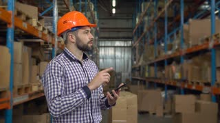 Manager working at warehouse. Handsome young man wearing casual shirt and hard hat using digital tablet entering data. Worker counting box for delivery