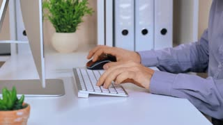 manager working on computer. unrecognizable busineess man sitting at the desk with flower pot folders and pc display