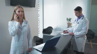 Medical workers standing at reception desk. Young caucasian nurse talking by phone with client. Adult doctor fill in medical records