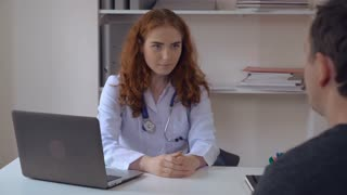 meeting in hospital. redhead woman doctor talking with patient man. Therapist wearing white coat and phonendoscope listening male in office