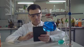 middle aged scientist working in chemical laboratory. Man wearing white coat using digital tablet