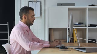 Mixed race man sitting at the working place in modern casual office. Adult businessman typing on computer. Professional businessman wearing casual shirt focused on screen pc works with documents or