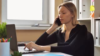 multitasking business woman sitting at the desk in small casual office talking with client by phone using computer giving consultation. attractive business female has negotiations by mobile