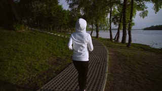 outdoors workout outside a big city. female runner in white hoodie has a morning jog.