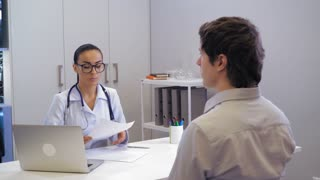 Patient sitting in the office doctor in clinic. Professional woman in white coat explain how to take pills and giving prescription