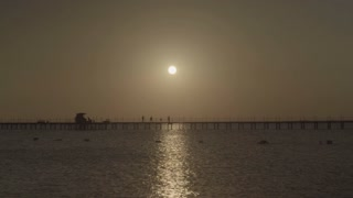 People are walking along the pier unhurriedly, a small wind stirs the water, the sun rises from the horizon