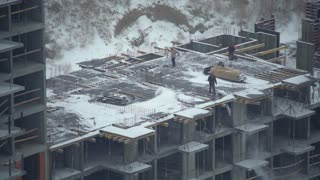 People working at a construction site. workers holding shovel and throw snow. Men wearing in orange coveralls and hard hat. view on the apartment house