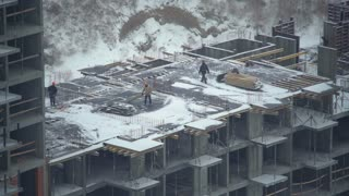 People working at under construction multi-storey building in winter season. employees clean snow using shovels