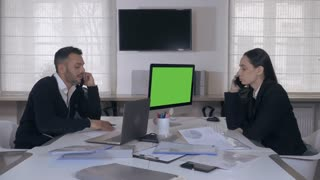 people working in office with modern white interior. attractive caucasian managers sitting at the desk has phone conversation. woman with long hair holding financial report with chart