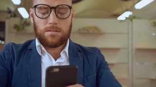 portrait adult businessman using smart phone messaging indoors. handsome man with red beard wearing casual jacket texting message at work or cafe chatting or sharing something or checking email or buy