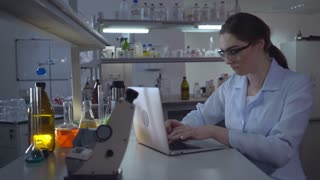 Portrait adult caucasian doctor working with laptop in laboratory. Chemist engineer or lab technician entering data on laptop. Professional woman working in the evening alone