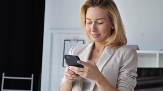 Portrait adult elegant woman using smartphone indoors. Smiling businesswoman wearing suit holding smart phone. Lady chatting in social media or use web application or shopping online. Happy cheerful