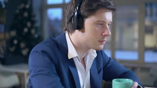 Portrait adult guy relaxing listening favorite playlist in office with big windows. Young businessman wearing in elegant fashionable jacket on head headphones