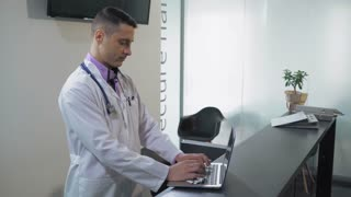 Portrait adult handsome doctor using laptop in clinic. Mixed race man wearing white coat typing on computer looking at the camera with friendly candid smile