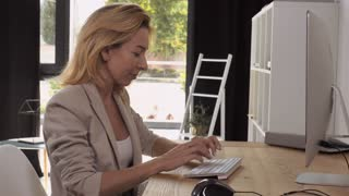 Portrait adult professional worker in office working with computer. Attractive blonde typing on keyboard sitting at the desk in room with casual interior. employee or entrepreneur entering data on pc