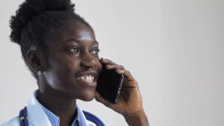 Portrait afro american doctor using smartphone talking with friendly smile. slow motion Young professional physician has phone conversation with patient or colleague in hospital. Woman wearing in