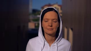 portrait attractive caucasian jogger. brunette wearing hood trains outdoor. close up face adult woman running in the morning