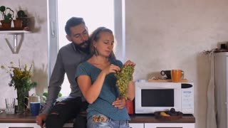 Portrait attractive young couple at home. Caucasian blonde woman and handsome man with beard and mustache eating grapes in the kitchen. Happy family in apartment