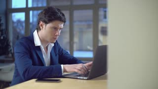 Portrait businessman focused on work. Handsome professional man typing fast on laptop. Caucasian model sitting at the desk indoors looking on screen computer