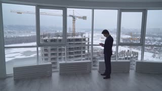 portrait busy businessman in the office near big panoramic windows with urban landscape in winter season. handsome caucasian male holding smartphone. successful young architect texting message in