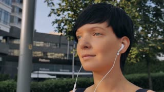 Portrait caucasian brunette listening music using earphone on the street in town sunny day. Adult female enjoy favorite song outdoors