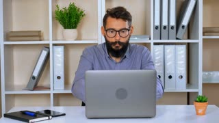 portrait funny man in the office. bearded worker looking at the camera yelling looking at the camera emotionally talking. businessman typing on laptop