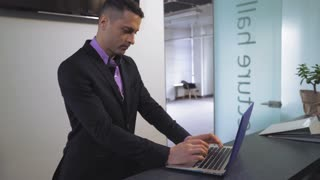 Portrait handsome employee standing at reception desk typing on laptop. Professional worker entering data on computer. Man wearing in suit