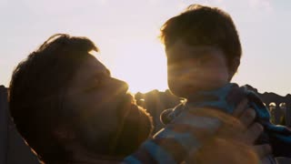 Portrait happy adult father with beard kissing son outdoors. Cheerful happy man holding child. Small boy looking on dad and smiling. Blissful fatherhood outdoors at sunset