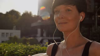 Portrait happy brunette drinking coffee using earphones on the street in the morning. Young woman with short hair cut enjoy daybreak alone