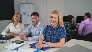 Portrait happy smiling people in the contemporary office. Young staff in startup company looking at the camera and smiling. Positive business team sitting at the working place and laughing