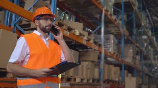 Portrait manager at work in warehouse has phone conversation with client. Handsome worker talking by smartphone discussing the logistics. Man wearing hard hat and orange vest