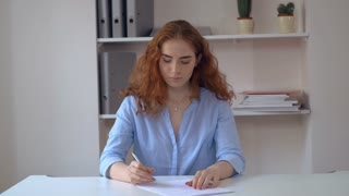 Portrait successful business woman with curly redheaded long hair sitting at the white desk in office sign document. Attractive female wearing casual elegant blue shirt undersign contract looking at