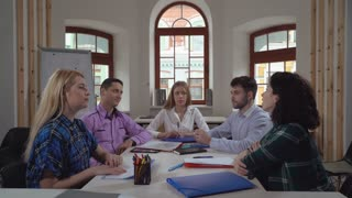 Portrait successful young business team in contemporary office. Diverse group of people at the meeting or brainstorming looking at the camera. Casual professional women and men sitting in boardroom