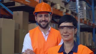 Portrait two workers at warehouse. Happy smiling co workers posing looking at the camera and smiling. Young professional woman and man wearing uniform high visibility orange hard hat ,vest