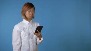 portrait young asian angy female screams at the phone on blue background in studio. attractive korean woman with blond hair wearing white casual shirt