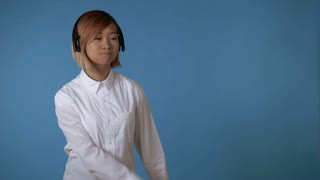 portrait young asian female dancing using headphones on blue background in studio. attractive korean woman with blond hair wearing white casual shirt looking at the camera with smile