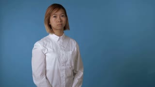 portrait young asian female posing showing hands gesture thumbs down on blue background in studio. attractive korean woman with blond hair wearing white casual shirt looking at the camera