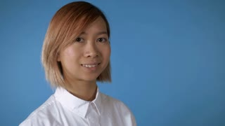 portrait young asian female posing showing hands gesture thumbs up on blue background in studio. attractive korean woman with blond hair wearing white casual shirt looking at the camera with smile
