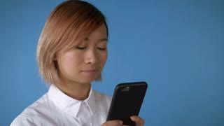 portrait young asian female posing using smartphone scrolling touch screen or messaging or posting in social media on blue background in studio. attractive korean woman with blond hair wearing white