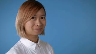 portrait young asian female posing winking on blue background in studio. attractive korean woman with blond hair wearing white casual shirt looking at the camera