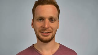 Portrait young caucasian man on grey background. caucasian guy with red hair posing showing hand gesture silence. handsome redhead men wearing in casual t-shirt