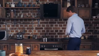 Portrait young muscular man eating breakfast looking at the camera. Businessman alone in the kitchen morning time
