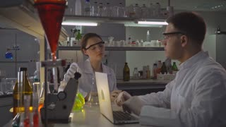 Professional adult woman and handsome man carrying out experiments and analyzing their findings. Female looking on the glass bulb. doctor typing on computer