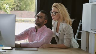 Professional business team discussing project looking on screen computer. Mixed race man and woman with blond hair talking smiling in modern office