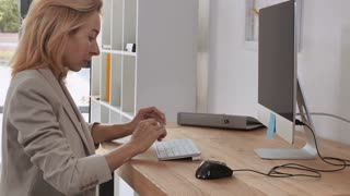 Professional successful manager with blond hair working in the office. Focused business woman typing on keyboard sitting at the desk with computer. Blonde adult female at work wearing elegant suit