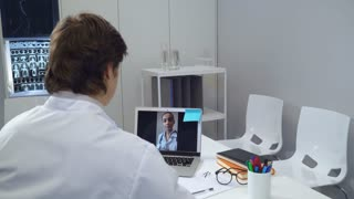 Professional woman md giving consultation online. Doctor talking with colleague using app on laptop
