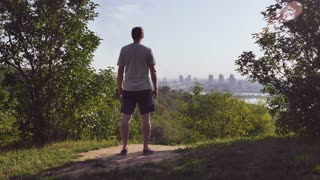 Rear back view man standing in park enjoy break of day looking on the city view. Male wearing casual sport wear alone in the morning outdoors. Summer season with beautiful fresh green nature