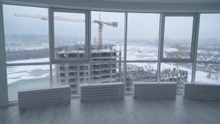 rear back view manager in real estate developer. employer in contemporary company looking through the windows in modern office on the construction site. urban landscape in winter season. man oversees