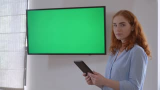 Redheaded manager standing near display with green screen on the wall. Businesswoman holding digital tablet. Female showing on the monitor